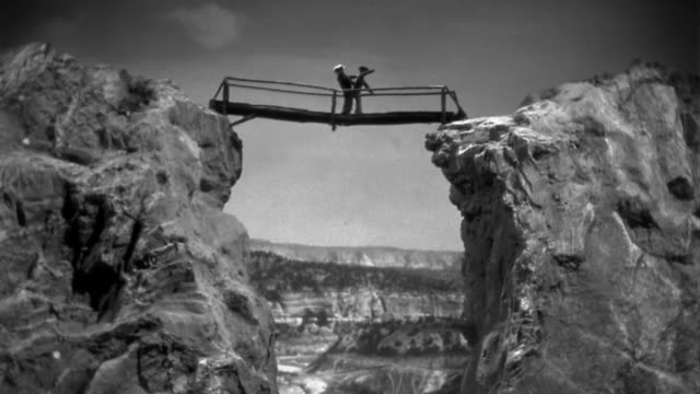 1940s wide shot bridge over 2 cliffs collapsing / dummies dangling from bridge / staged - collapsing stock videos & royalty-free footage