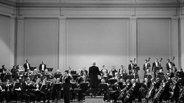 1940s wide shot conductor leading full orchestra in concert performance on stage - orchestra stock videos & royalty-free footage
