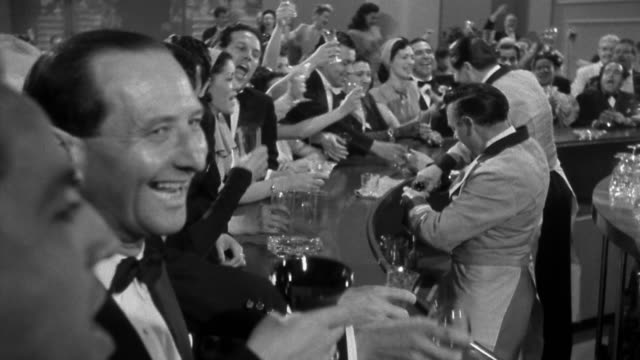 vídeos y material grabado en eventos de stock de 1940s wide shot crowd of formally attired men and women at bar talking, laughing  / bartenders pouring - blanco y negro