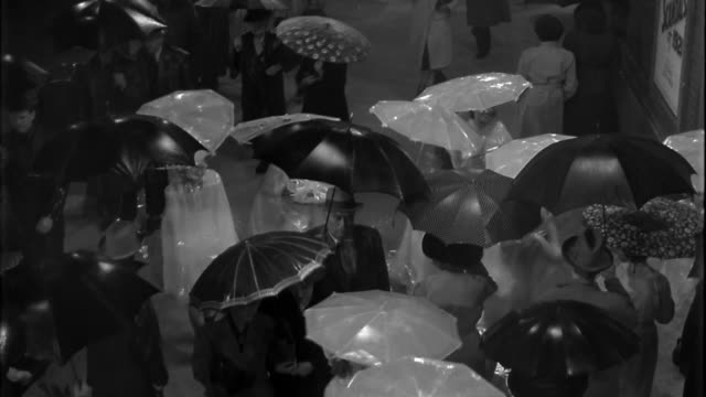 1940s wide shot dolly shot women in white rain ponchos and umbrellas dancing in rain through crowd to theater front - waterproof clothing stock videos & royalty-free footage
