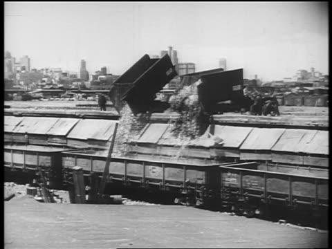 b/w 1940s wide shot dumptrucks unloading scrap metal into large bins / city skyline in background / newsreel - ゴミ収集車点の映像素材/bロール