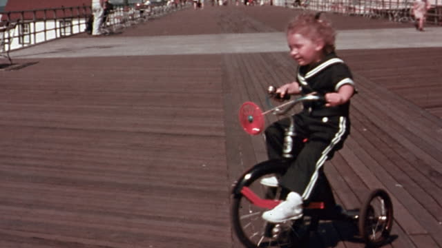 1940s wide shot girl in sailor suit riding tricyle in circles on boardwalk - sailor suit stock videos and b-roll footage