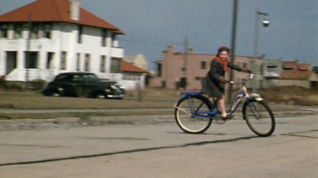 vídeos y material grabado en eventos de stock de 1940s wide shot girl riding bicycle on street / turning / riding toward cam - bicicleta vintage