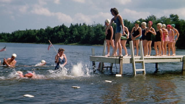 1940s wide shot girl taking her turn jumping from dock into water and swimming at summer camp - life belt stock videos & royalty-free footage