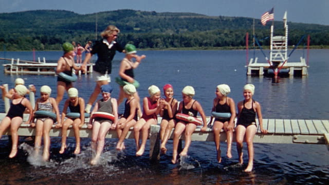 1940s wide shot line of girls in swim suits sitting on dock / camp counselor leading 2 girls to end of line - summer camp helper stock videos & royalty-free footage