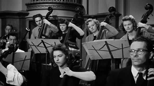 1940s wide shot musicians play double basses and cellos in string section during orchestral perfomance