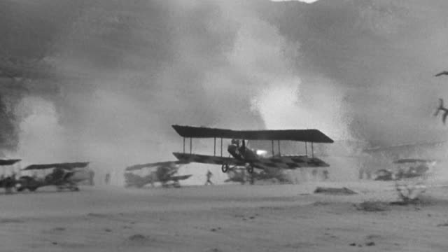 1940s wide shot pan German biplane taking off with cockpit on fire and crashing / people running in background
