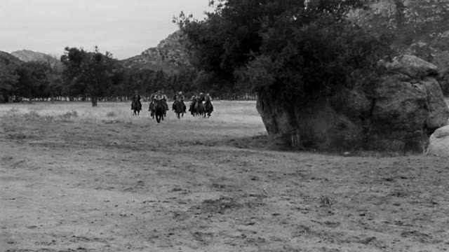 1940s wide shot pan group of cowboys riding across prairie on horseback - recreational horse riding stock videos and b-roll footage