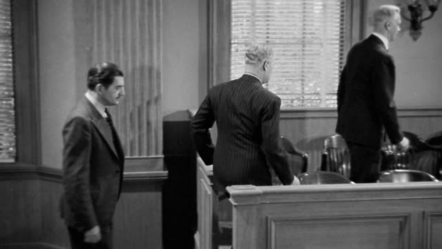 1940s wide shot pan twelve male and female jurors walking into courtroom, standing + sitting down in jury box - legal trial stock videos & royalty-free footage