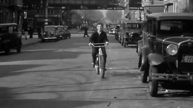 1940s wide shot teenage boy riding bicycle toward cam on city street / elevated tracks in background - 1940 stock videos and b-roll footage