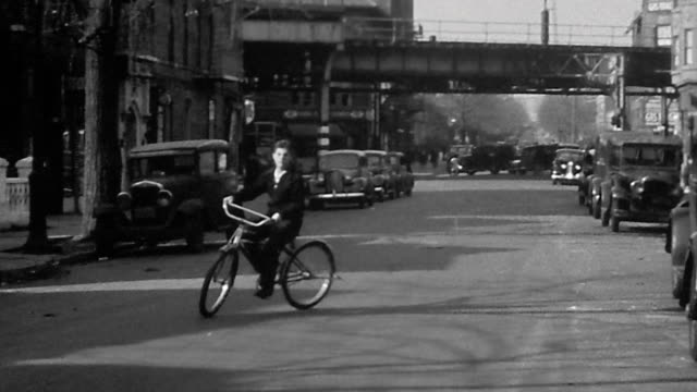 1940s wide shot teenage boy swerving bicycle toward cam on city street / elevated train tracks in background - elevated train stock videos & royalty-free footage