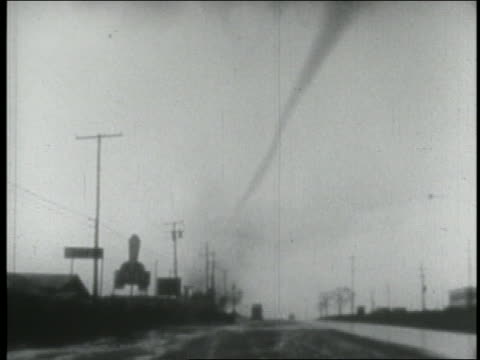 B/W 1940s wide shot tornado spinning over road lined with telephone poles