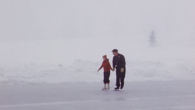 1940s wide shot tracking shot man and girl skating on ice rink together - single father stock videos & royalty-free footage