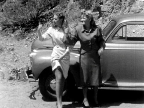 1940s wide shot two women showing leg while hitchhiking on roadside/ one woman removes skirt/ audio - stockings stock videos & royalty-free footage