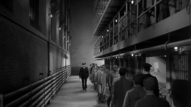 vidéos et rushes de 1940s wide shot uniformed guard and prisoners walking along cell block inside jail - prison