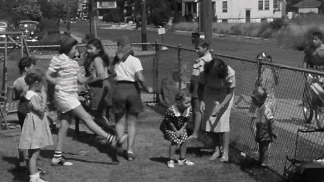 1940s wide shot young woman dancing with group of girls in fenced front yard - nassau stock videos & royalty-free footage