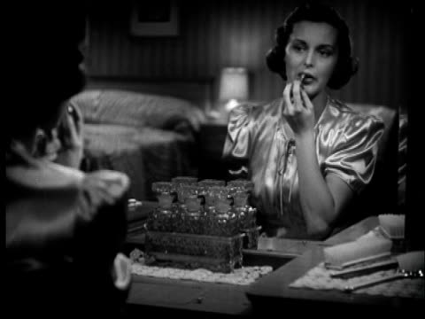 b/w montage 1940s woman applying lipstick in front of mirror - make up stock videos & royalty-free footage