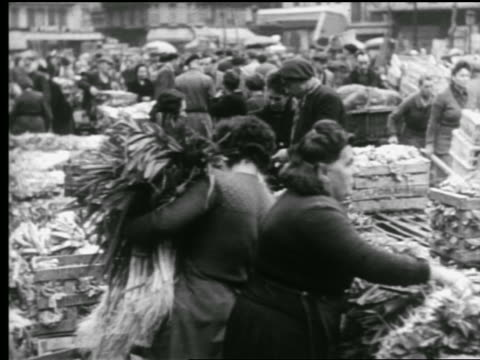 vidéos et rushes de b/w 1940s woman carrying vegetables by produce stands in busy outdoor market / paris, france - âges mélangés