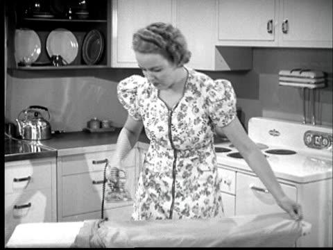 b/w montage 1940s woman ironing and man  laying bricks - アイロン点の映像素材/bロール