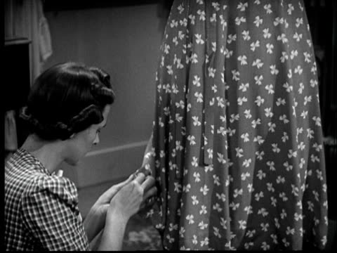 b/w cu tu 1940s woman sewing dress on annoyed man - hausfrau stock-videos und b-roll-filmmaterial