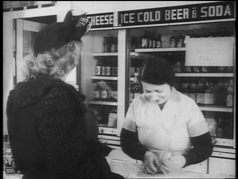 b/w 1940s woman waiting at grocery store counter as cashier takes ration stamps / newsreel - food stamps stock videos & royalty-free footage