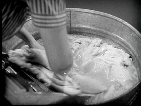 B/W CU 1940s Woman's hands washing clothes with scrub board