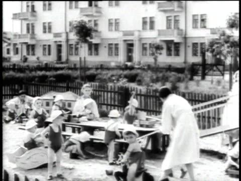 1940s WS women taking care of children on playground / Russia