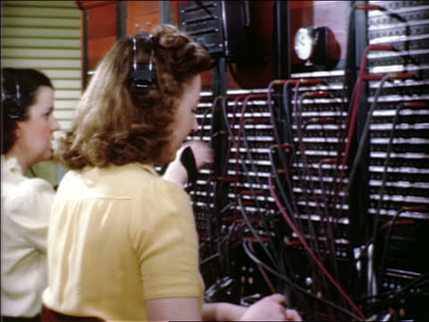 1940s women telephone operators working at switchboard - 電話交換機点の映像素材/bロール