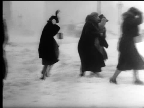 b/w 1940s pan women walking on snow covered sidewalks during blizzard / chicago - gale stock videos and b-roll footage