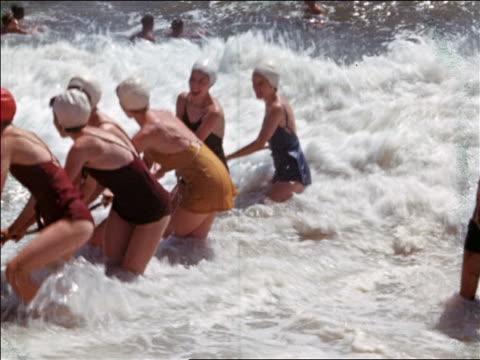 vídeos y material grabado en eventos de stock de 1940s women/teen girls in swimsuits and bathing caps hold onto rope in surf / home movie - sólo chicas adolescentes