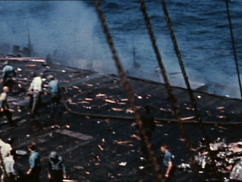 1940s wwii high angle wreckage of japanese plane on deck of uss intrepid / pan crew extinguishing fires - hospital corpsman点の映像素材/bロール