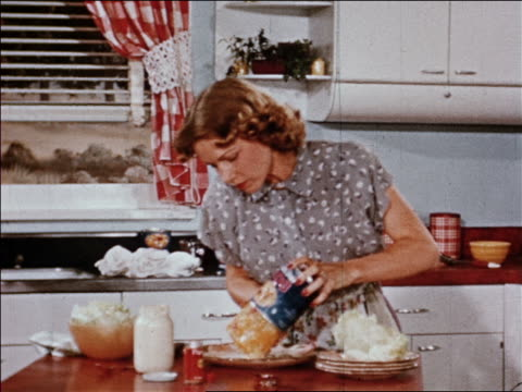 1940s zoom in housewife pours fruit salad gelatin mold from can to plate then starts slicing it / indust. - gelatin stock videos & royalty-free footage