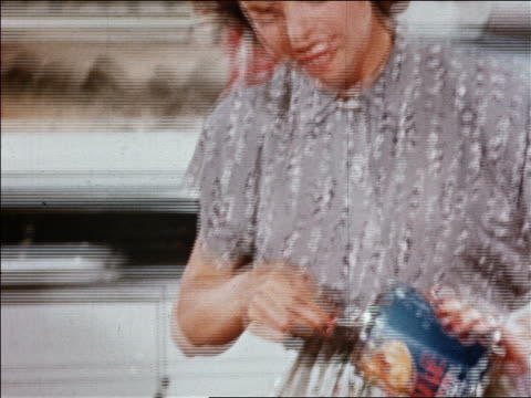 1940s zoom out zoom in housewife holds can of dole fruit cocktail then pours it into bowl on kitchen counter - canned food stock videos & royalty-free footage