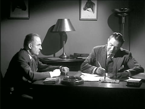 b/w 1940s/50s businessman at desk writes on pad of paper then shows it to other man - employee engagement stock videos & royalty-free footage
