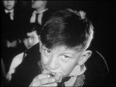 B/W 1940s/50s close up boy eating doughnut in contest / newsreel