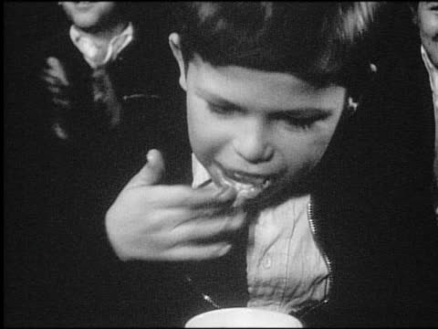 b/w 1940s/50s close up boy eating doughnut in contest / newsreel - newsreel stock videos and b-roll footage