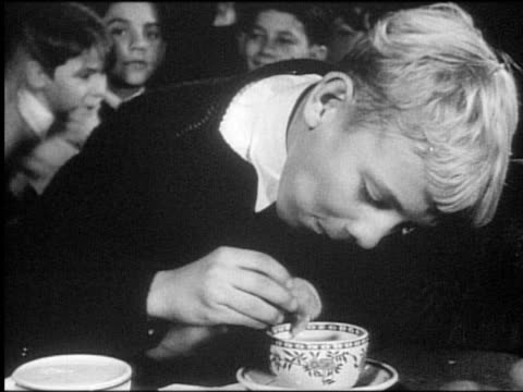 b/w 1940s/50s close up boy eating doughnut in contest / newsreel - doughnut stock videos & royalty-free footage