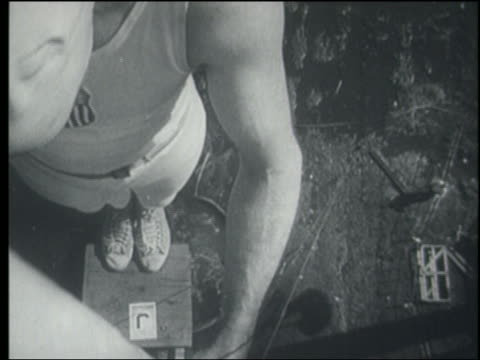 B/W 1940s/50s close up man standing on diving board high above ground / flaming vat below him