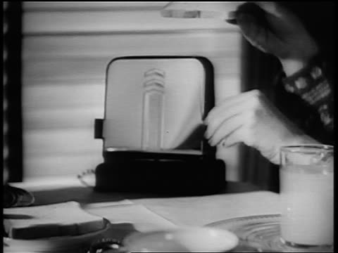 b/w 1940s/50s close up woman's hands putting piece of bread in toaster with flip-down door - toaster appliance stock videos & royalty-free footage