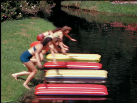 1940s/50s four women in swimsuits jumping onto inflatable rafts in lake / Cypress Gardens, Florida