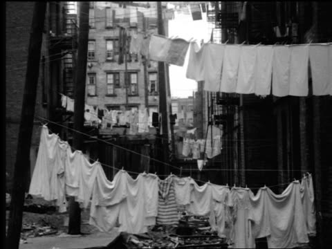 B/W 1940s/50s laundry hanging from clotheslines between tenement buildings in city