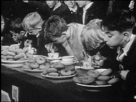 B/W 1940s/50s line of boys at table eating doughnuts in contest / newsreel