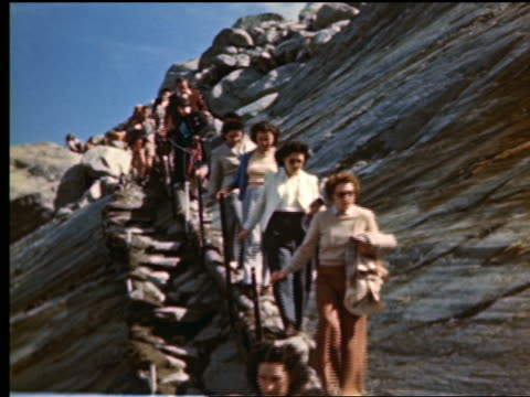 1940s/50s line of people going down steep side of mountain (mont blanc?) in french alps / france - historisch stock-videos und b-roll-filmmaterial