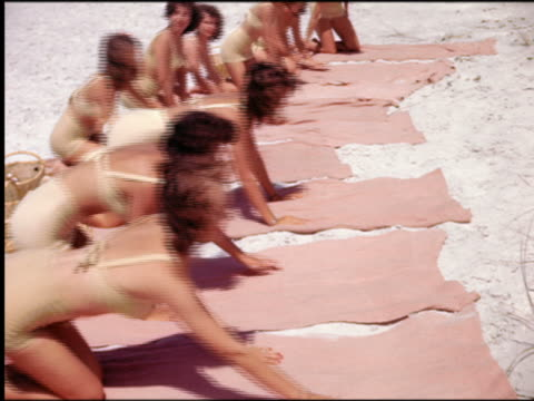 vídeos de stock, filmes e b-roll de 1940s/50s line of women in identical swimsuits lying down on towels on beach / st petersburg, fl - biquíni