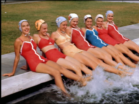 1940s/50s line of women in swimsuits + bathing caps sitting on edge of pool kicking legs in water