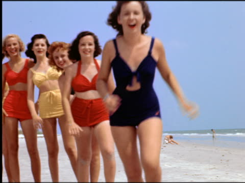 vídeos de stock, filmes e b-roll de 1940s/50s line of women in swimsuits running toward + jumping over camera on beach / st petersburg - biquíni
