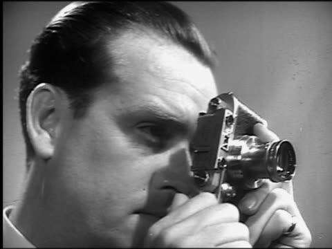 vídeos de stock e filmes b-roll de b/w 1940s/50s low angle close up man taking photograph with camera - fotografando