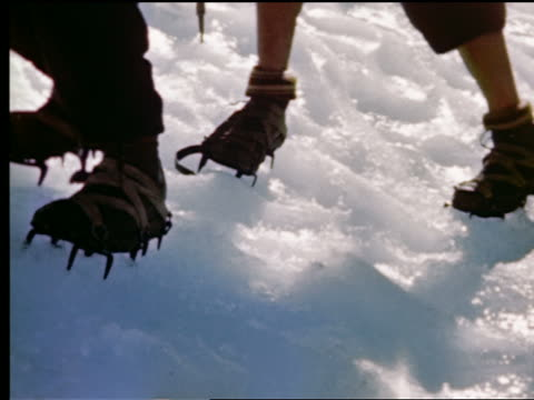 1940s/50s low angle close up mountain climbers walking across ice field on side of mountain (mont blanc?) in french alps with crampons tied around boots / france - shoes in a row stock videos & royalty-free footage