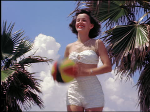 1940s/50s low angle smiling woman in swimsuit throwing beachball outdoors / st petersburg, florida - bikini stock videos & royalty-free footage