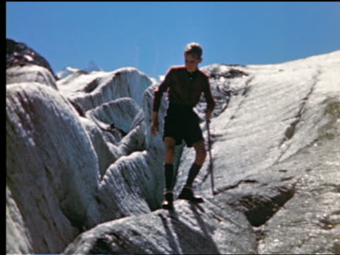 1940s/50s low angle teen boy going down steep side of mountain (mont blanc?) + chipping ice with pickaxe in french alps / france - low stock videos and b-roll footage